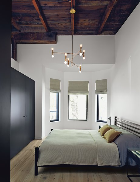 The master bedroom includes an armoire by Kastella and a chandelier by Lambert & Fils. A portion of the ceiling was pared back to expose the underside of the original roof.