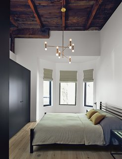 Scandinavian Style Revives This Montreal Home - Photo 9 of 14 - The master bedroom includes an armoire by Kastella and a chandelier by Lambert & Fils. A portion of the ceiling was pared back to expose the underside of the original roof.