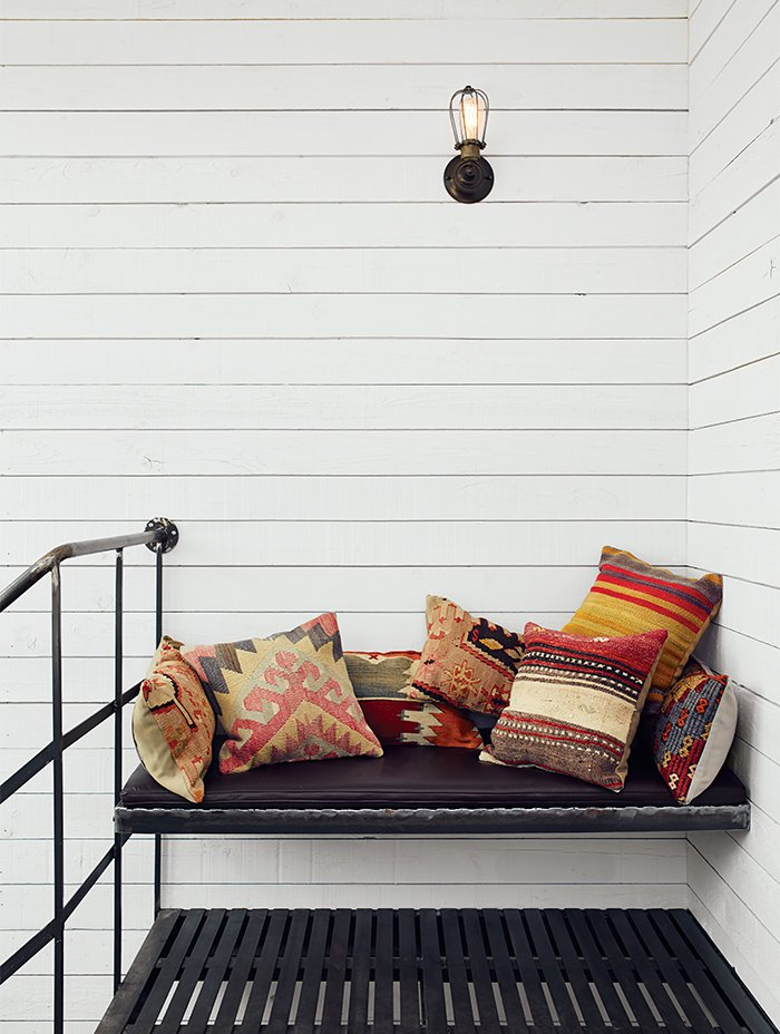 Atop the spiral staircase, a custom iron bench is festooned with Turkish throw pillows from SophiesBazaar. Scandinavian Style Revives This Montreal Home - Photo 12 of 14