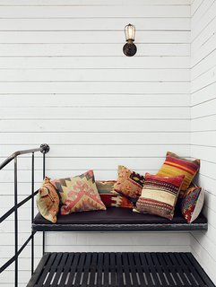 Scandinavian Style Revives This Montreal Home - Photo 12 of 14 - Atop the spiral staircase, a custom iron bench is festooned with Turkish throw pillows from SophiesBazaar.
