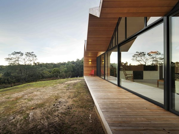 "Constructing a largely timber house in a bush fire-prone landscape wasn't easy. ""We had to negotiate with the council and building surveyor,"" Crump explains. To solve the challenge, the architect designed an outer, protective skin for the home that's clad with metal; it pushes beyond the building envelope to provide covering for outdoor living spaces. The inset walls are lined with local shiplap Celery Top Pine."