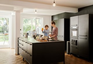We Can't Get Enough of This German Apartment's Sleek Matte-Black Kitchen - Photo 2 of 11 - The island serves as a generous workspace for Dorothee to prepare dishes with her son Morten. The couple's updates to the 1967 apartment included introducing large windows to the garden and covering the floors with an oak parquet to match the original flooring in a couple of rooms.