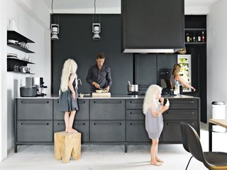 "10 Stunning Ways to Use Black in Your Kitchen - Photo 3 of 10 - Twin daughters Merle and Anine join their parents in the family's kitchen, designed by Jensen for Vipp. He explains that his role as chief designer at Vipp is to ""work with their DNA"" by refining the company's trademark materials: stainless steel, painted metal, and rubber. For the utilitarian kitchen, ""we wanted to get the feeling of a tool,"" he says. ""It's nice to have a space where you can actually work."" The gas stovetop is by ABK and the refrigerator is by Smeg; Le Perroquet spotlights are from iGuzzini."