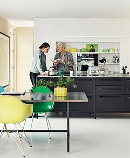 The couple have crafted their own kitchens in the past. For their floating home, however, they selected the black Vipp kitchen, where Juul chats with her daughter, Karla.