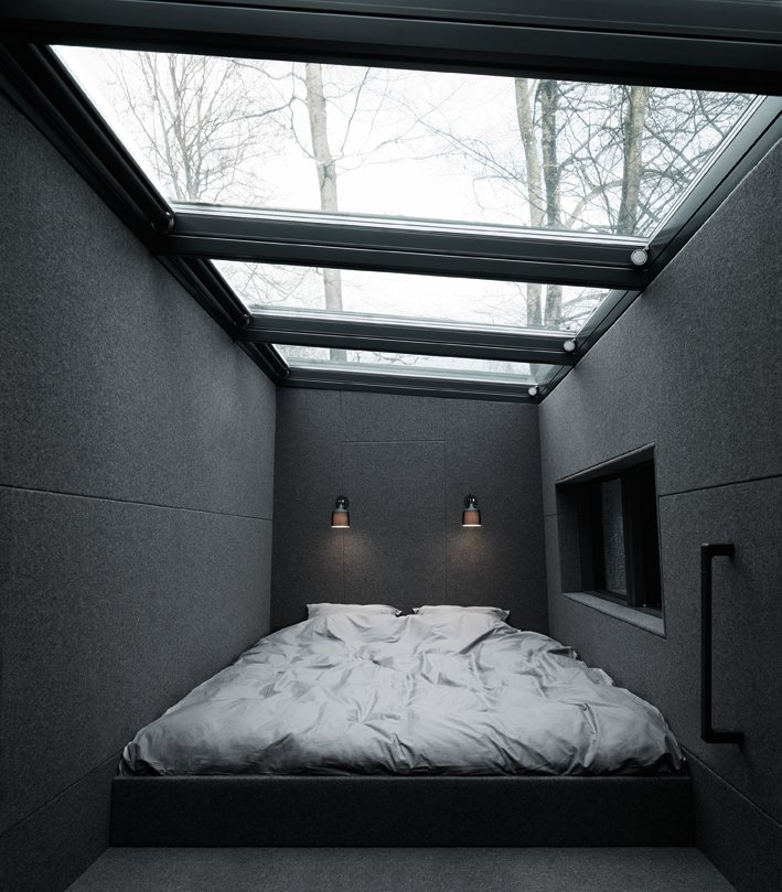 A Velux skylight above the sleeping loft includes remote-controlled integrated blinds. The prefab unit can sleep up to four people between the bed loft and the lower-level daybed. Tagged: Bedroom.  Prefab Homes by Dwell from Prefab Gets a Makeover With Danish Industrial Design