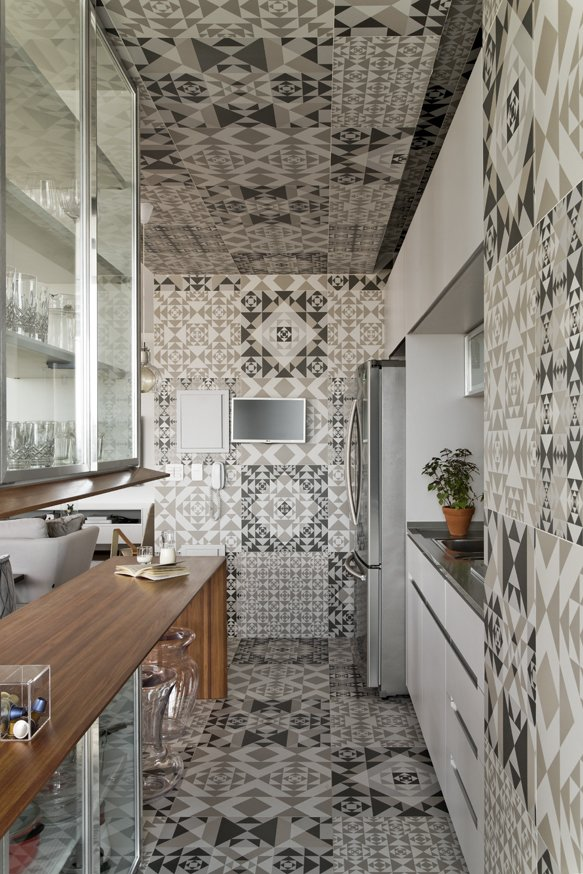 The graphic tile covers the floor, walls, and ceiling. The kitchen millwork was done by Inovart Carpentry.