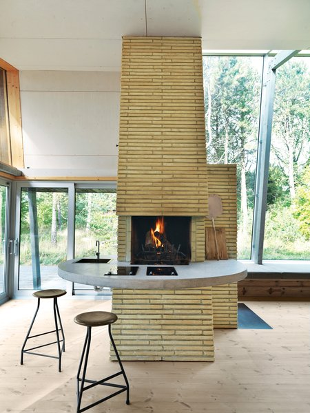Inside, life revolves around the brick chimney, which the architect surrounded with a concrete counter that wraps from the kitchen to the living area. The stools are vintage.