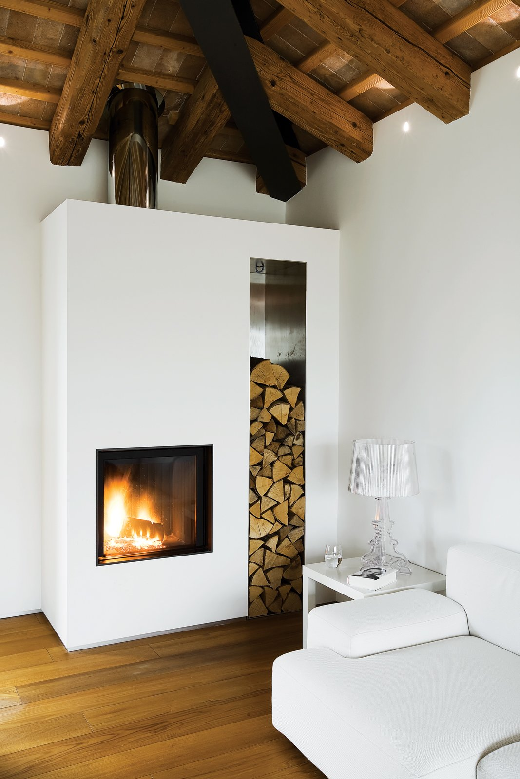 A firewood nice and hearth infuse the interior of a renovated farmhouse in Italy with coziness. Photo by Helenio Barbetta. Tagged: Living Room, Medium Hardwood Floor, End Tables, Sofa, Table Lighting, and Wood Burning Fireplace.  97+ Modern Fireplace Ideas by Dwell from A Renovated Farmhouse in Northern Italy