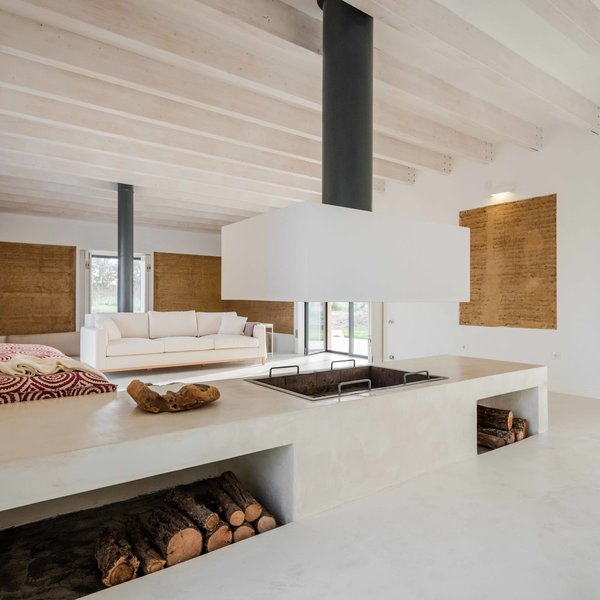 Known for its thermal properties, rammed earth helps maintain a mild temperature all-year-long. A large fireplace is used to warm the living area in winter.