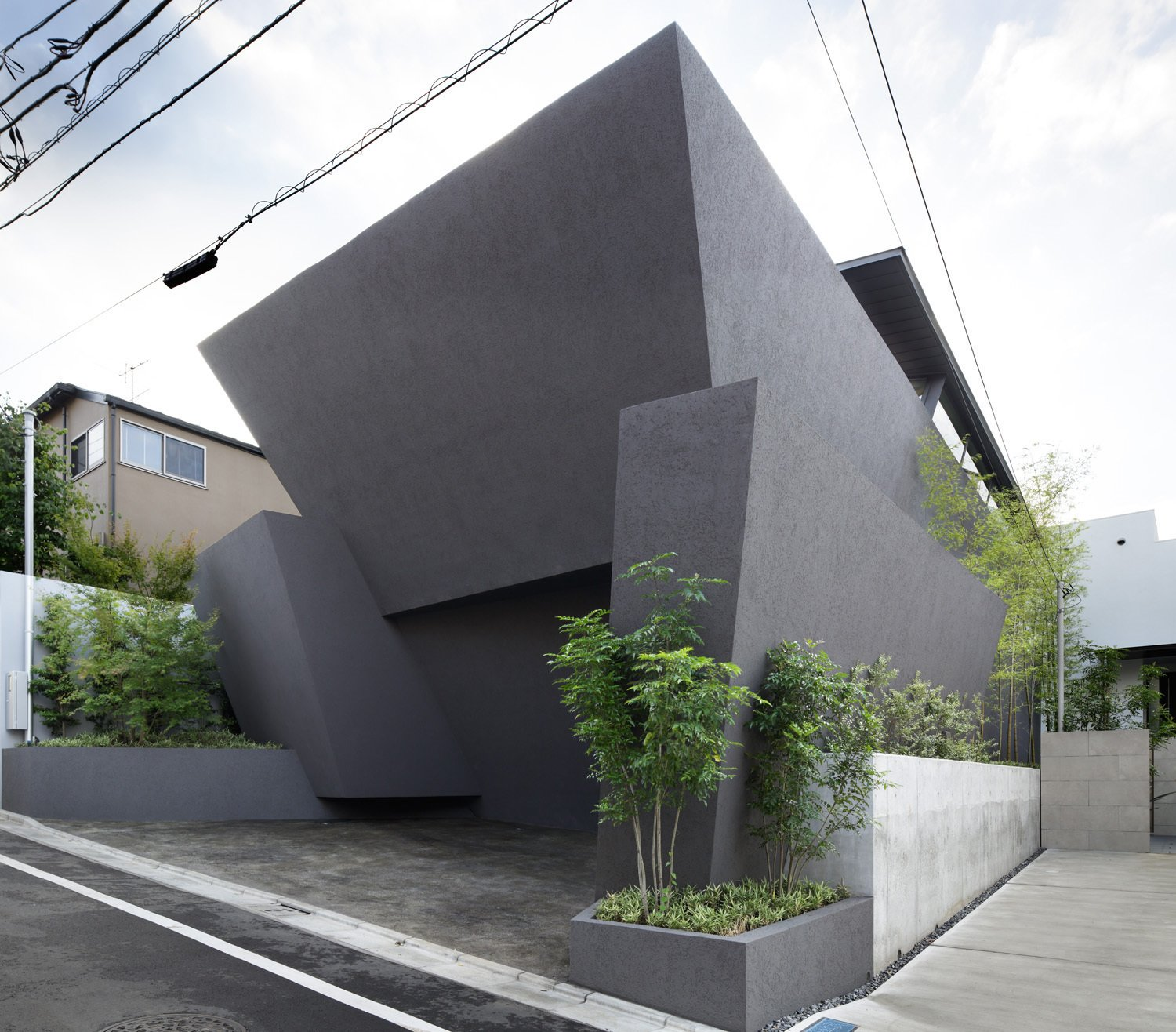 Concrete planters frame the facade—a union of monolithic slabs that offers privacy and compositional integrity to the building. The exterior is a plaster finish over insulation and concrete. Japanese Homes by Dwell