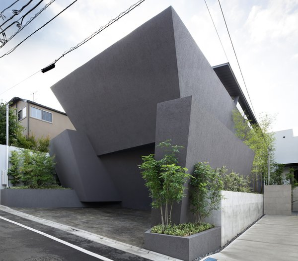 Concrete planters frame the facade—a union of monolithic slabs that offers privacy and compositional integrity to the building. The exterior is a plaster finish over insulation and concrete. Photo  of SRK modern home