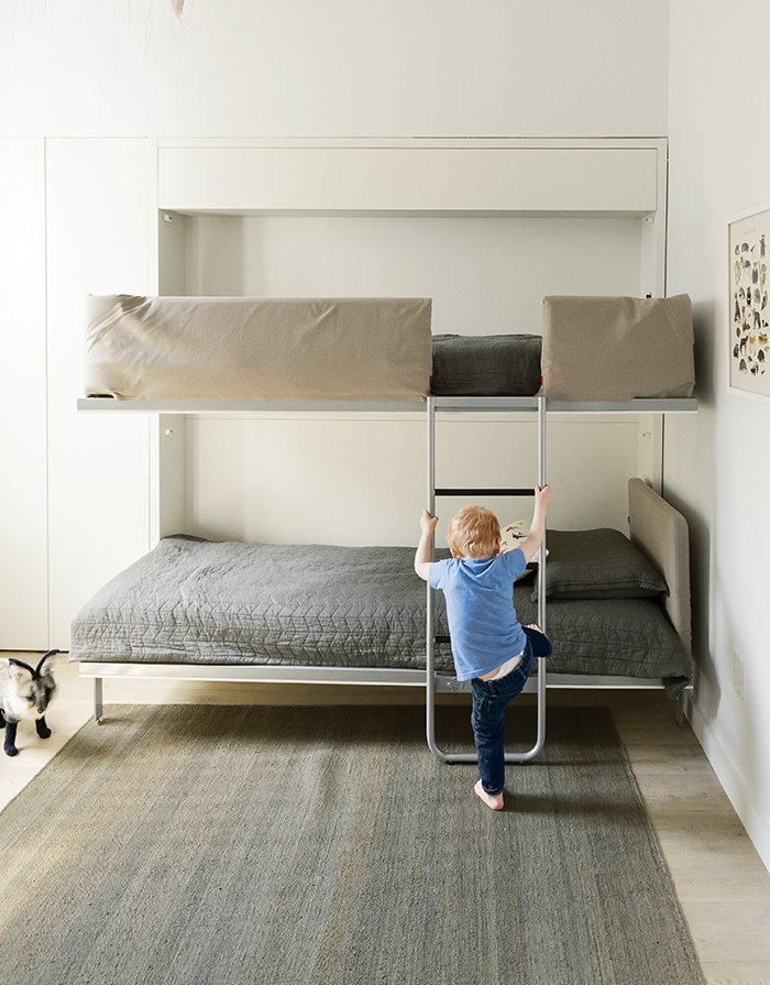 The bunk bed, the Lollipop IN model from Resource Furniture, stows away flush to the wall when not in use. Tagged: Kids Room, Bedroom, Playroom, and Boy Gender.  Photo 5 of 14 in How One Family of Three Does It All in 675 Square Feet from How to Take a Dwell Photo