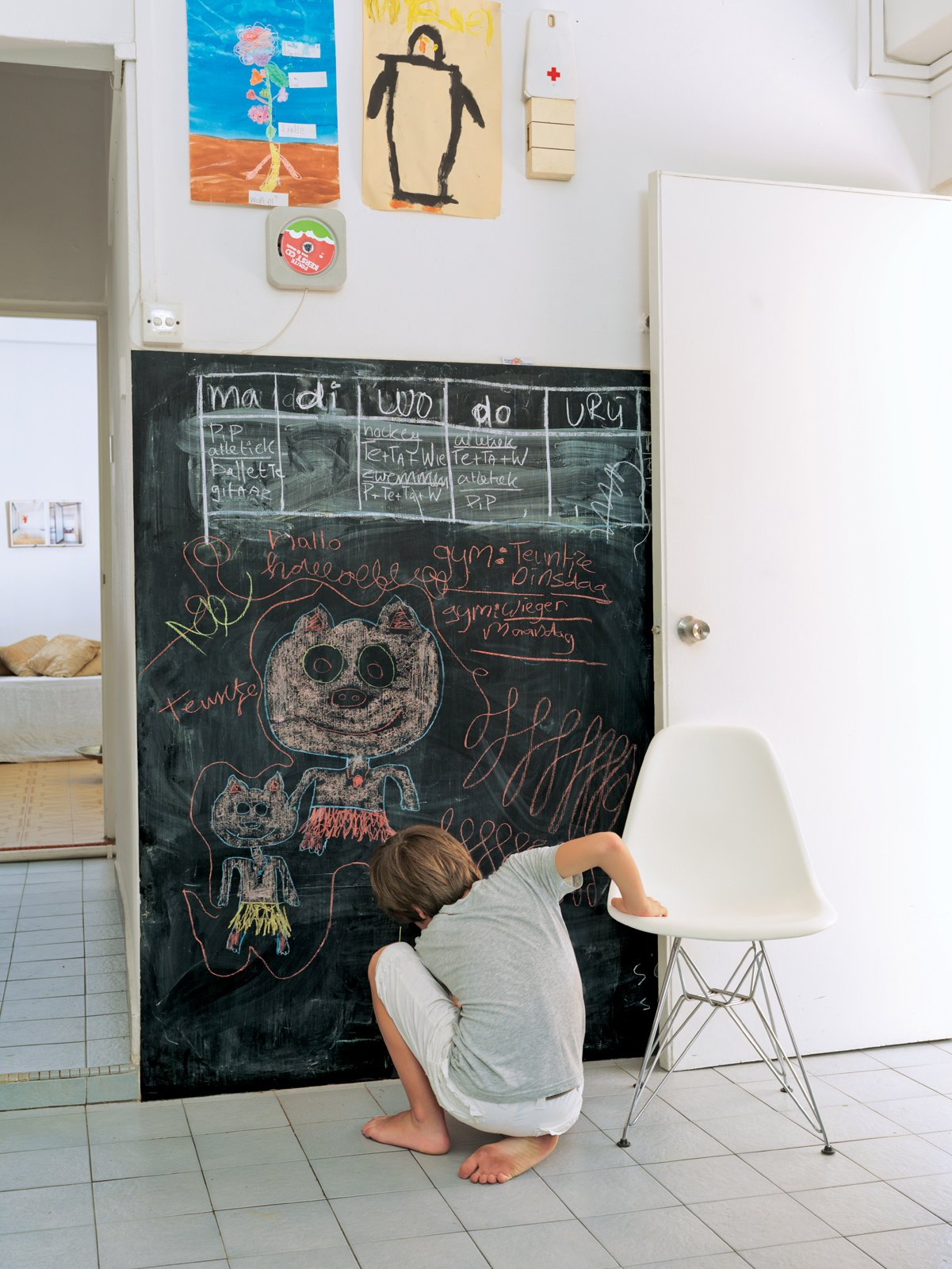 De Waart added a chalkboard to the kitchen for writing memos and for drawing, as Tammo does here. Tagged: Living Room and Chair.  Photo 4 of 11 in A Family Moves from Netherlands to Singapore