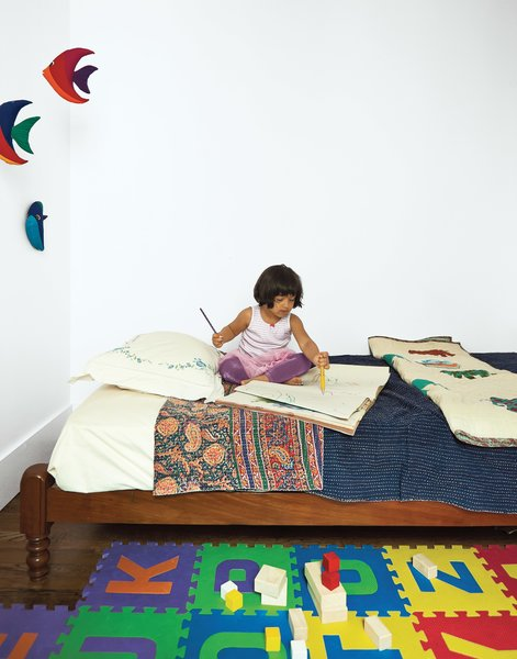 A traditional Indian twin bed in Mira's room is outfitted in hand-stitched linens from Fabindia in Delhi. The toy blocks are from KID-O.