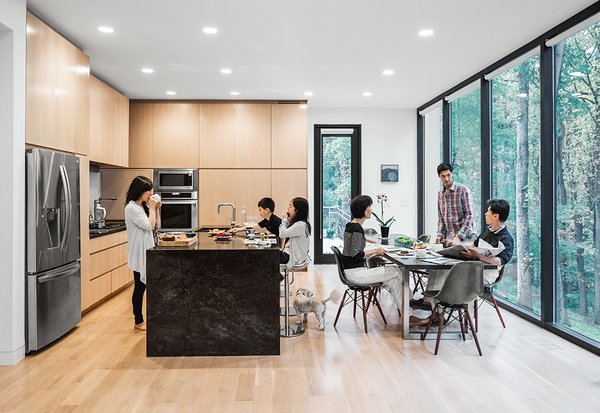 Equipped with an LG refrigerator and Thermador wall oven, the eat-in kitchen also boasts custom cabinets faced with an oak veneer and a natural stone island.  Photo 6 of 11 in This Woodland Home in Virginia Was Built for Modern, Multigenerational Living