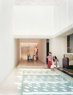 The dining area feels like an extension of the pool, with water channels on two sides.