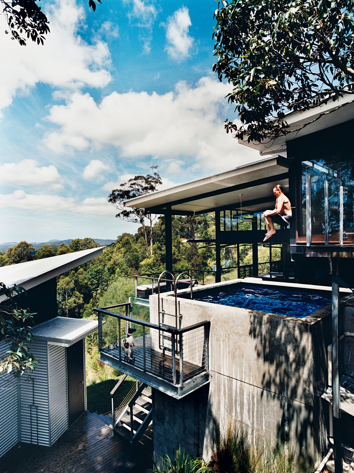 Dunlop demonstrates the deck's secondary use: as a launching pad into the concrete plunge pool on the first floor. Tagged: Outdoor, Plunge Pools, Tubs, Shower, Swimming Pools, Tubs, Shower, Small Patio, Porch, Deck, Concrete Pools, Tubs, Shower, and Small Pools, Tubs, Shower.  Photo 12 of 12 in Hillside Family Home in Australia