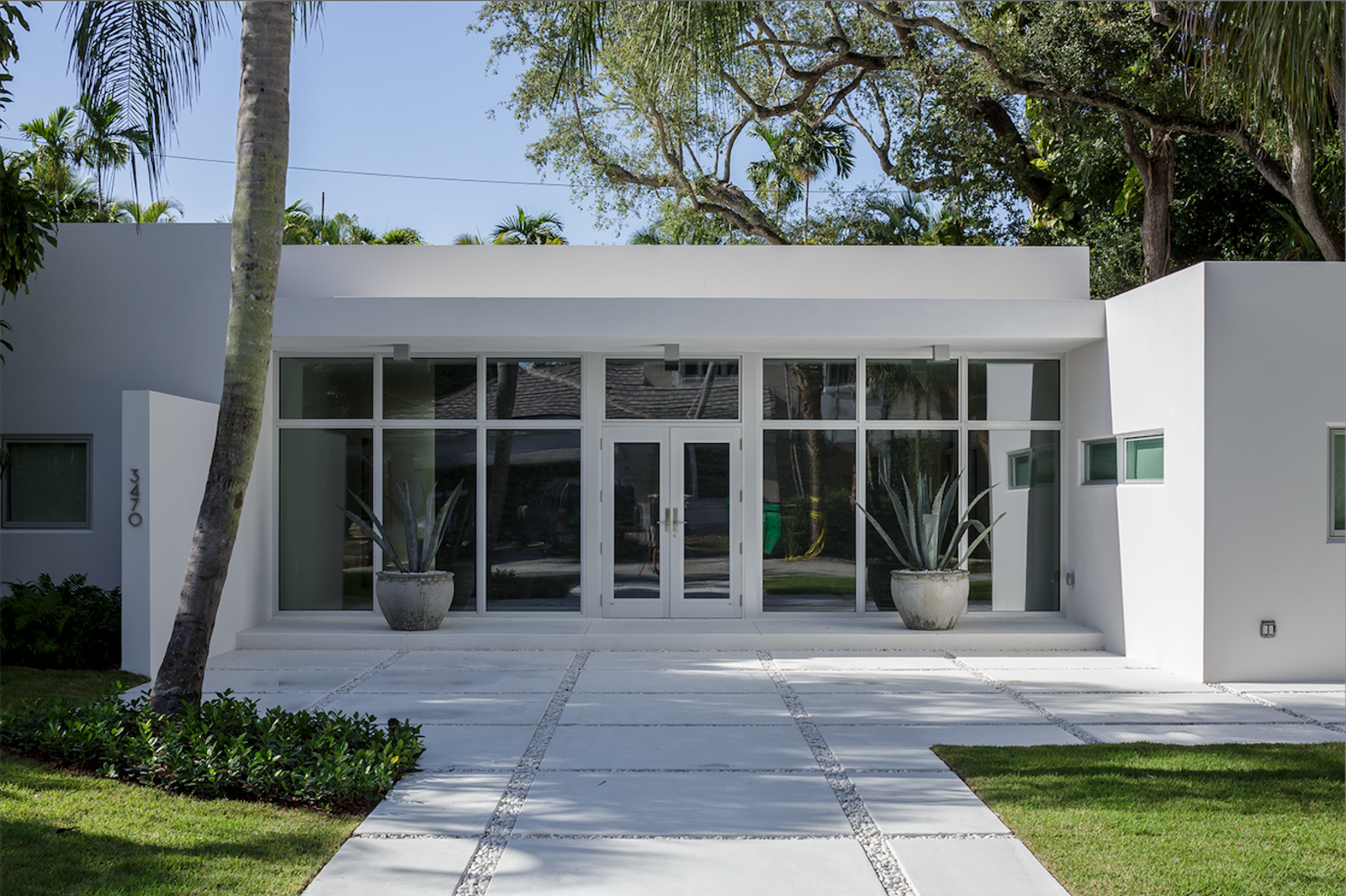 The home's potential for outward expansion was limited, so new glass doors and windows were installed in a storefront configuration (a decision not common to residential construction) to provide ample natural light for the main entrance.  Photo 1 of 11 in 10 Fantastically Sleek Foyer Designs from All-White Homes in Scorching Hot Climates