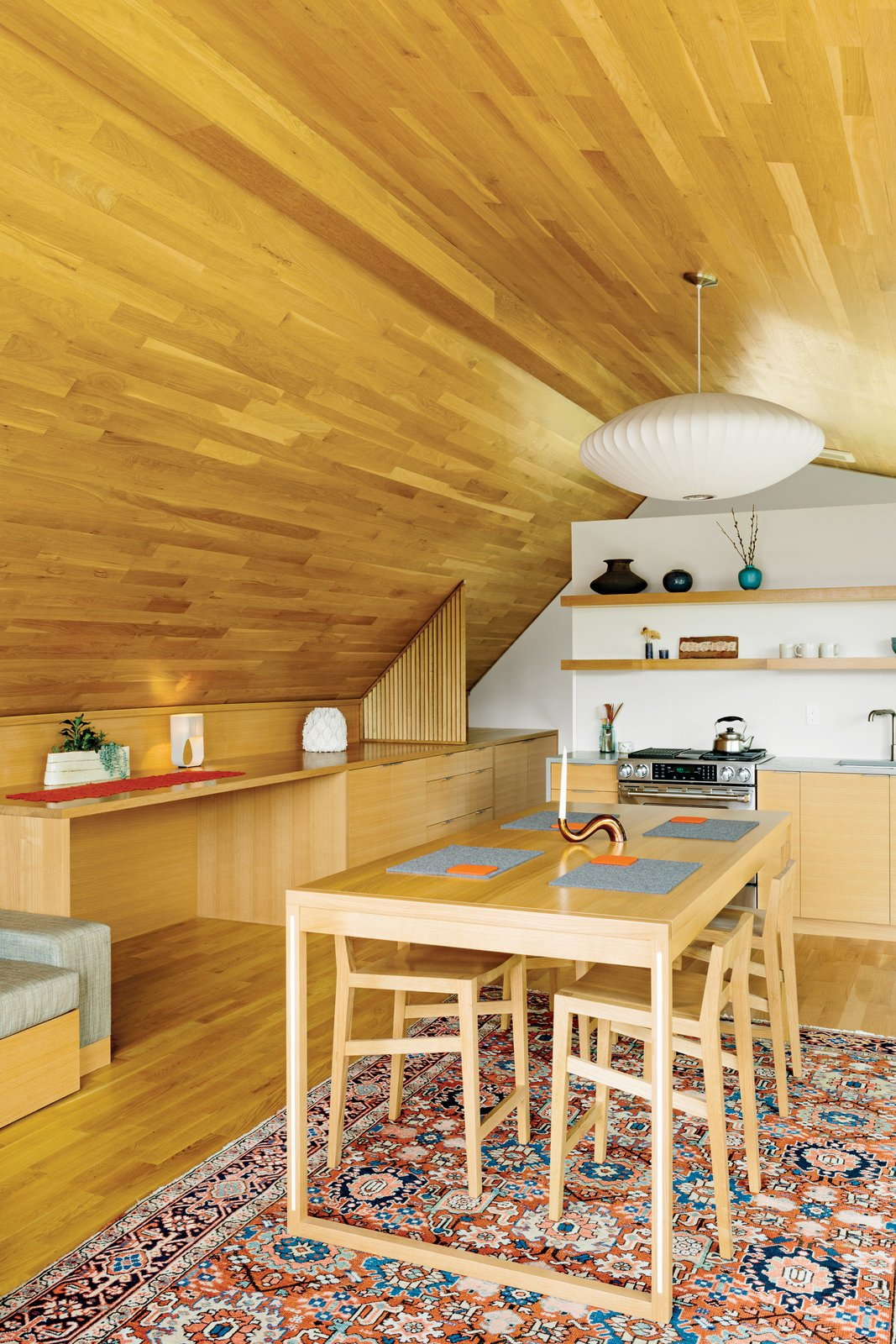 Strips of white-oak flooring line the interior of the studio, created by designer Jeff Vincent and PATH Architecture. The George Nelson Bubble Lamp Saucer pendant is available at the Dwell Store; the kitchen cabinets and appliances are by Jenn-Air. All accessories are from Canoe and Relish. Tagged: Dining Room, Chair, Table, Pendant Lighting, Rug Floor, and Light Hardwood Floor.  Best Photos from Salvaged Wood Renovation in Portland