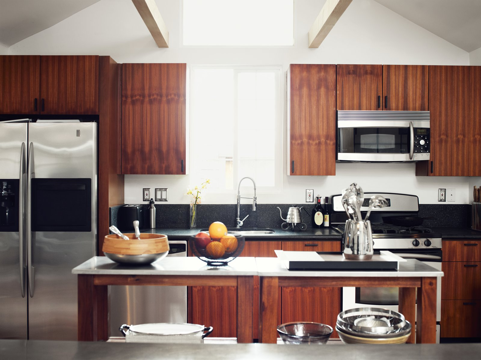 He worked with Kartheiser's existing appliances in the kitchen, trading the old cabinetry for new teak. Tagged: Kitchen, Wood Cabinet, Granite Counter, Undermount Sink, Refrigerator, and Microwave.  Photo 7 of 14 in Inspired Indoor Teak Looks from The Tiny Hollywood Home of Mad Men's Vincent Kartheiser