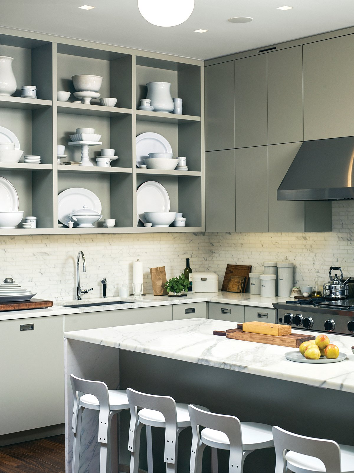 """Custom kitchen cabinets designed by Pulltab and fabricated by Maciek Winiarczyk hold mostly vintage ironstone that Geiger has found at flea markets and estate sales over the past 20 years. """"I love white,"""" she says, """"because I think food always looks better on it."""" She also collects vintage wooden cutting boards, shown resting against the marble tile backsplash from Stone Source. Tagged: Kitchen, Marble Counter, Marble Backsplashe, Range Hood, Range, and Open Cabinet.  Photo 11 of 21 in 20 Dream Kitchens from Smart Space-Saving Kitchen Designs"""