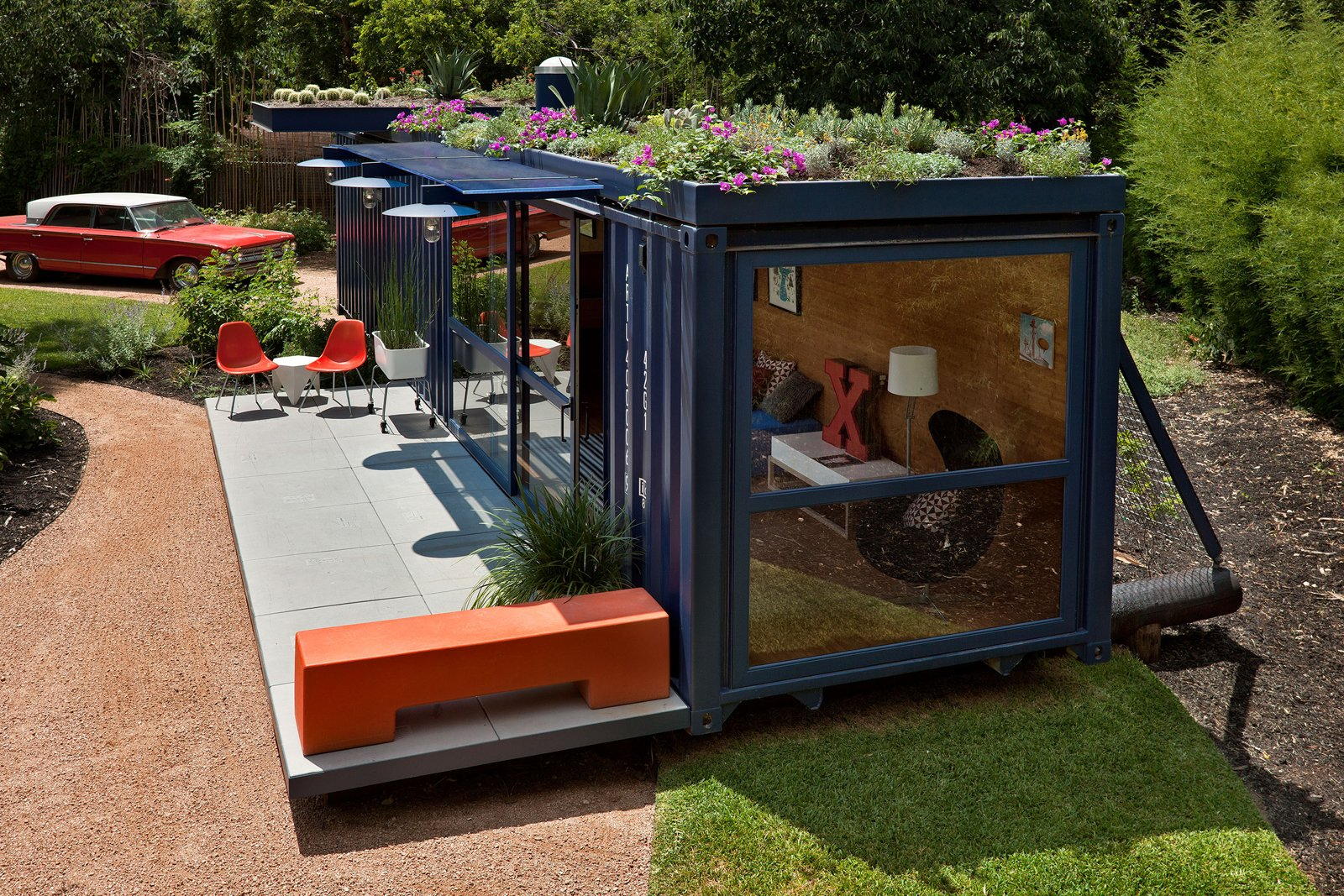 Jon Ahrens of Madrone Landscaping, who layed out the plantings around the container, implemented a green roof on a drip watering system. The cantilevered overhang at rear is planted with cacti.  Shipping Containers by Dwell from Smaller in Texas