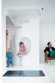 "Light-Filled Family Home Renovation in Copenhagen - Photo 4 of 23 - Resident Peter Østergaard (with Maja, 6, and Carl, 20 months) and architect and photographer Jonas Bjerre-Poulsen have been best friends since they were 13, which makes for easy collaboration. Says Bjerre-Poulsen: ""There are always a lot of challenges in a renovation, but Peter and Åsa trusted my judgment and gave me a completely free hand. Usually it's hard to push people into unconventional solutions, but Peter has all these wild and crazy ideas."" One such idea was to embed a transparent glass-and-iron door in the floor, operated by a hydraulic pump, which allows access to the subterranean wine cellar. At night, the lit-up cellar glows, lending the compact living room an increased sense of verticality."