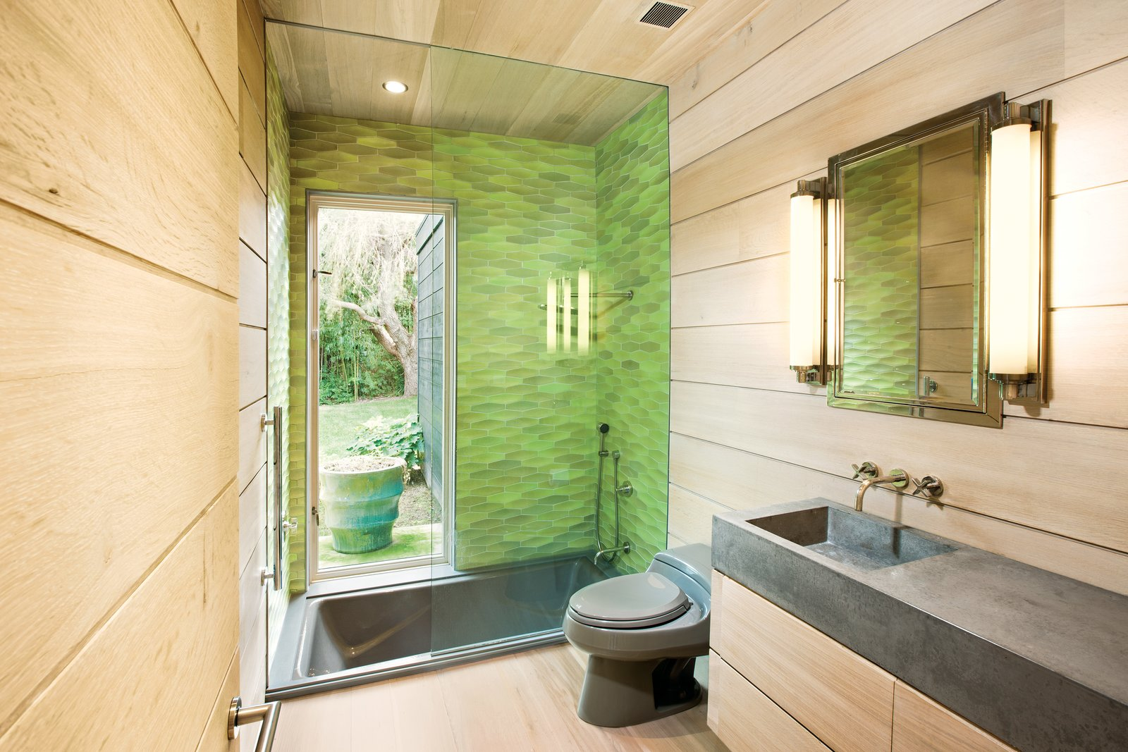 In the bathroom, Martin selected Heath Ceramics Conclave Diamond tile in citrus green for the glass-enclosed Kohler tub, which is outfitted with nickel Kallista fixtures. A matching toilet by Kohler   in the color Cashmere blends with the custom-fabricated concrete sink by Get Real Surfaces. Photo by Patrick Bernard.
