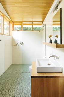 In the bathroom, a thin pane of glass separates the shower; an Aquaplane sink by Lacava hovers above <br><br>a built-in vanity illuminated by a lean Adelphi light by Oxygen Lighting; and blue-green glass penny tiles by Terra Verre decorate the floor. The absence of a door, combined with windows on two sides, makes the bathroom feel like a continuation of the overall space.