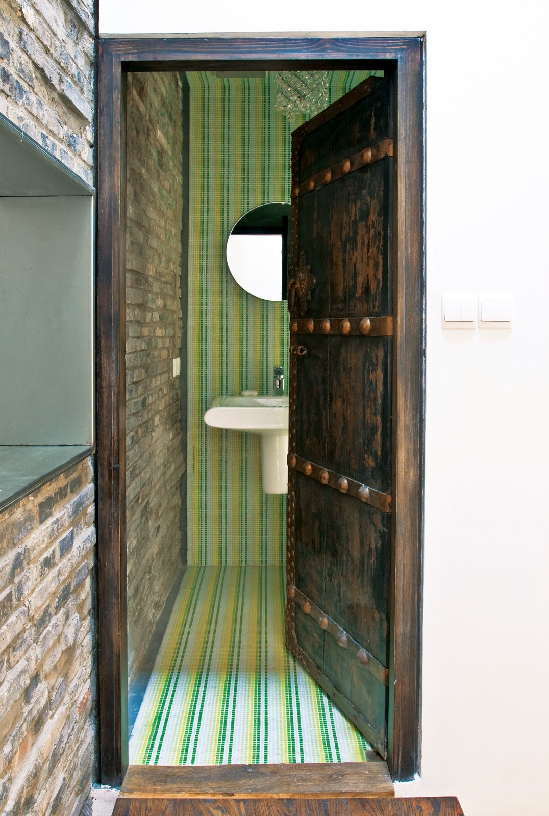 Carbone preserved many of the home's original bones while replacing the roof and plumbing and shoring up the structure. The interior spaces, too, mix new and old. Allegranti found many of the furnishings and fixtures in nearby markets, including the antique doors used in his bathroom and closet. Modern Lilong House Renovation in Shanghai - Photo 3 of 11