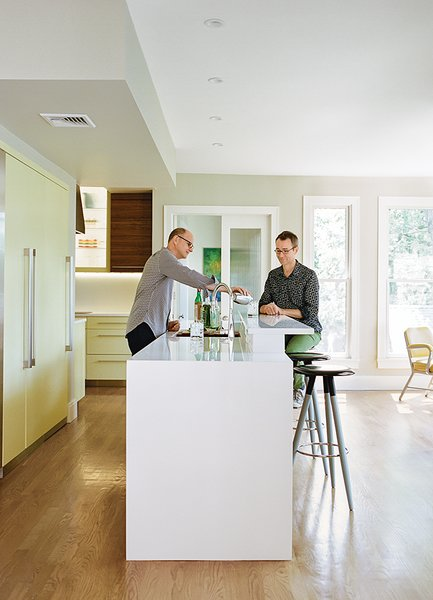 "Dan Pacek, left, and John Roynon prepare cocktails at their 12-foot ""display island"" in the renovated kitchen of their home in New Jersey. The couple bought handles matching those on their Thermador refrigerator and used them on a set of pantry doors, one of which conceals the steps to the basement."
