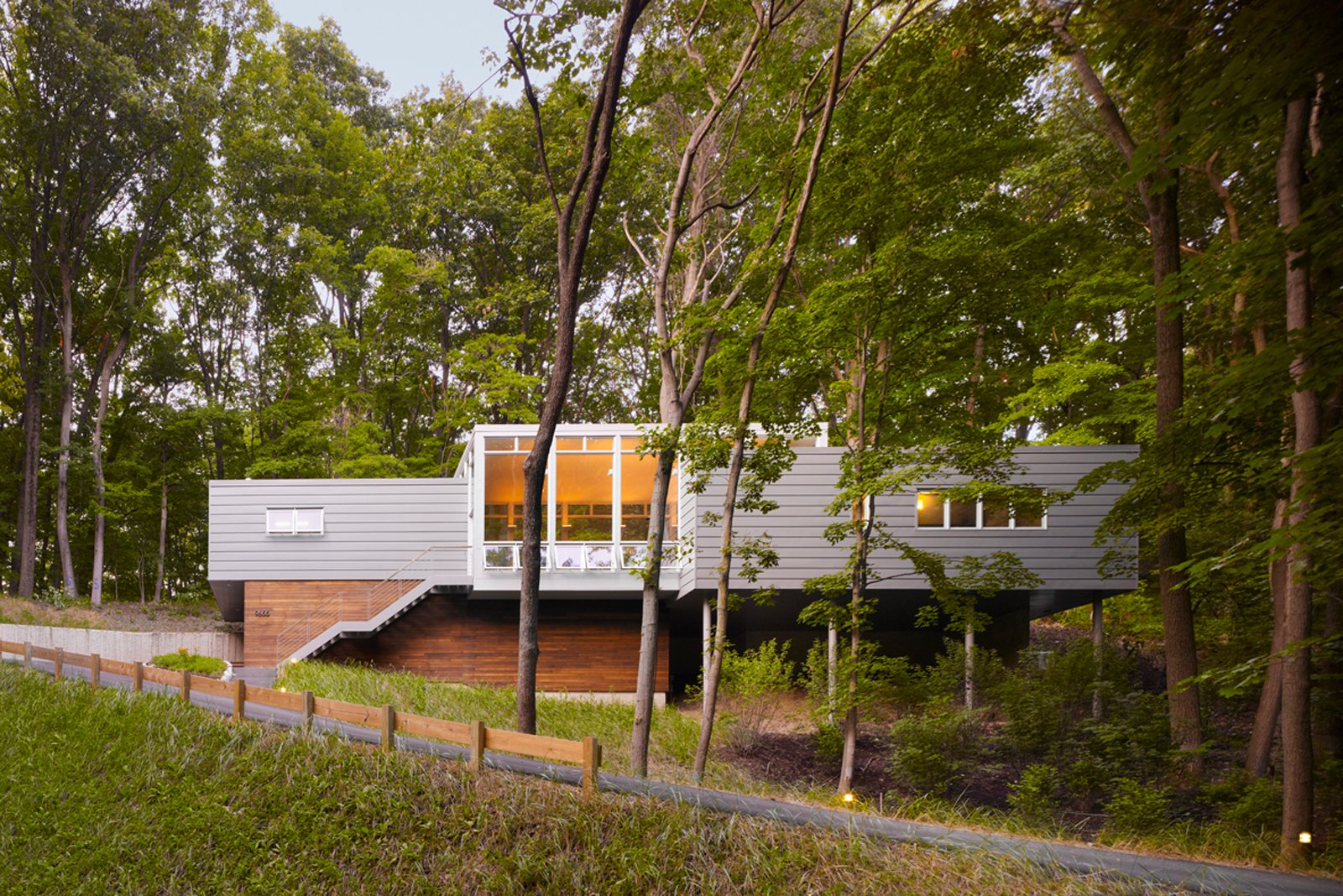 """Built on a challenging hillside site and tucked behind a thicket of trees, the Bridgman, Michigan, house designed by Scott Rappe provides a modern weekend retreat for a Chicago couple. """"One of my first responsibilities was getting the owners up to their house and essentially on one level. Because of the pie-shaped property, we needed to push the building up the hill to provide square footage for the program. By keeping the building perpendicular to the slope, using piloti on one side and a retaining wall on the dune side, we were able to insert foundations with minimal disturbance,"""" says Rappe."""