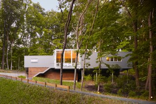 "20 Modern Homes From the Midwest - Photo 6 of 20 - Built on a challenging hillside site and tucked behind a thicket of trees, the Bridgman, Michigan, house designed by Scott Rappe provides a modern weekend retreat for a Chicago couple. ""One of my first responsibilities was getting the owners up to their house and essentially on one level. Because of the pie-shaped property, we needed to push the building up the hill to provide square footage for the program. By keeping the building perpendicular to the slope, using piloti on one side and a retaining wall on the dune side, we were able to insert foundations with minimal disturbance,"" says Rappe."