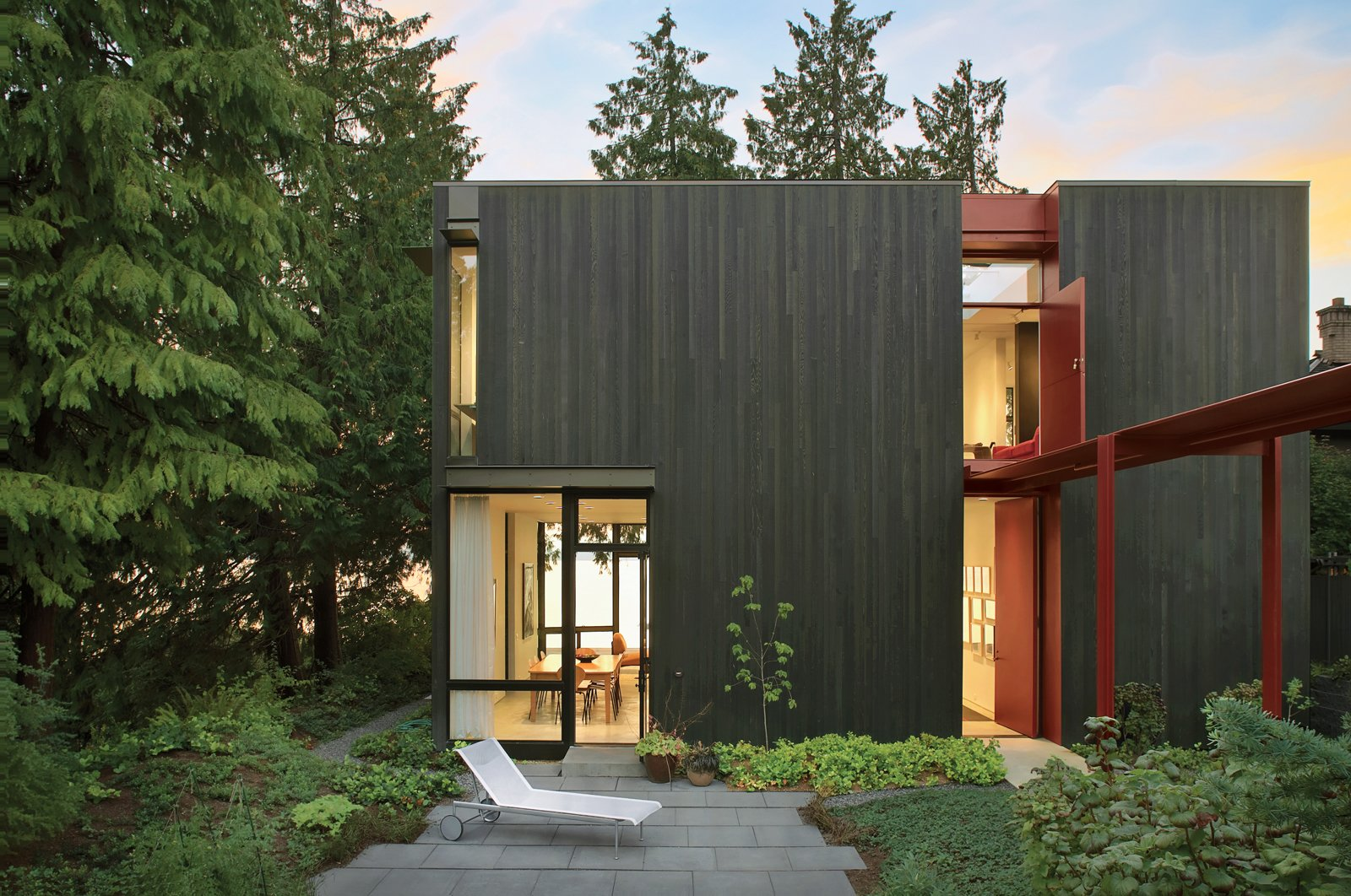 """A second-story Dutch door above the canopy ushers in sunlight and breezes. """"Light is really important in the Pacific Northwest because it's dark for most of the year,"""" says the resident. The cedar-clad facade is pierced with thoughtfully placed windows, which frame views and """"actively engage the idiosyncratic nature of the place,"""" says architect Tom Kundig.  House of Steel  by Diana Budds from Modern Steel Homes"""