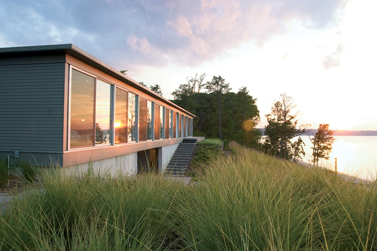 """Ziger/Snead Architects constructed this ode to rowing in rural Virginia for a Baltimore couple who share a love of sculling. """"Everywhere in the house you can see the moment where land meets water,"""" says Douglas Bothner, an associate at the firm. Tagged: Exterior, House, Wood Siding Material, Concrete Siding Material, and Metal Siding Material.  Photo 2 of 2 in Row House"""