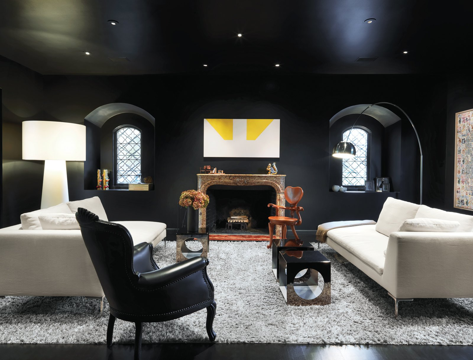 Turin embraced the dark in her striking living room—the deep paint is Le Corbusier's 4320J from Les Couleurs Suisse. An iconic Arco lamp by Achille and Pier Giacomo Castiglioni for Flos, Charles sofas by Antonio Citterio for B&B Italia, an Extra Big Shadow floor lamp by Marcel Wanders for Cappellini, and a painting over the mantel by Martin Barré shed a little light.  Living Rooms by Lara Deam from A Traditional Home and an Impeccable Eye