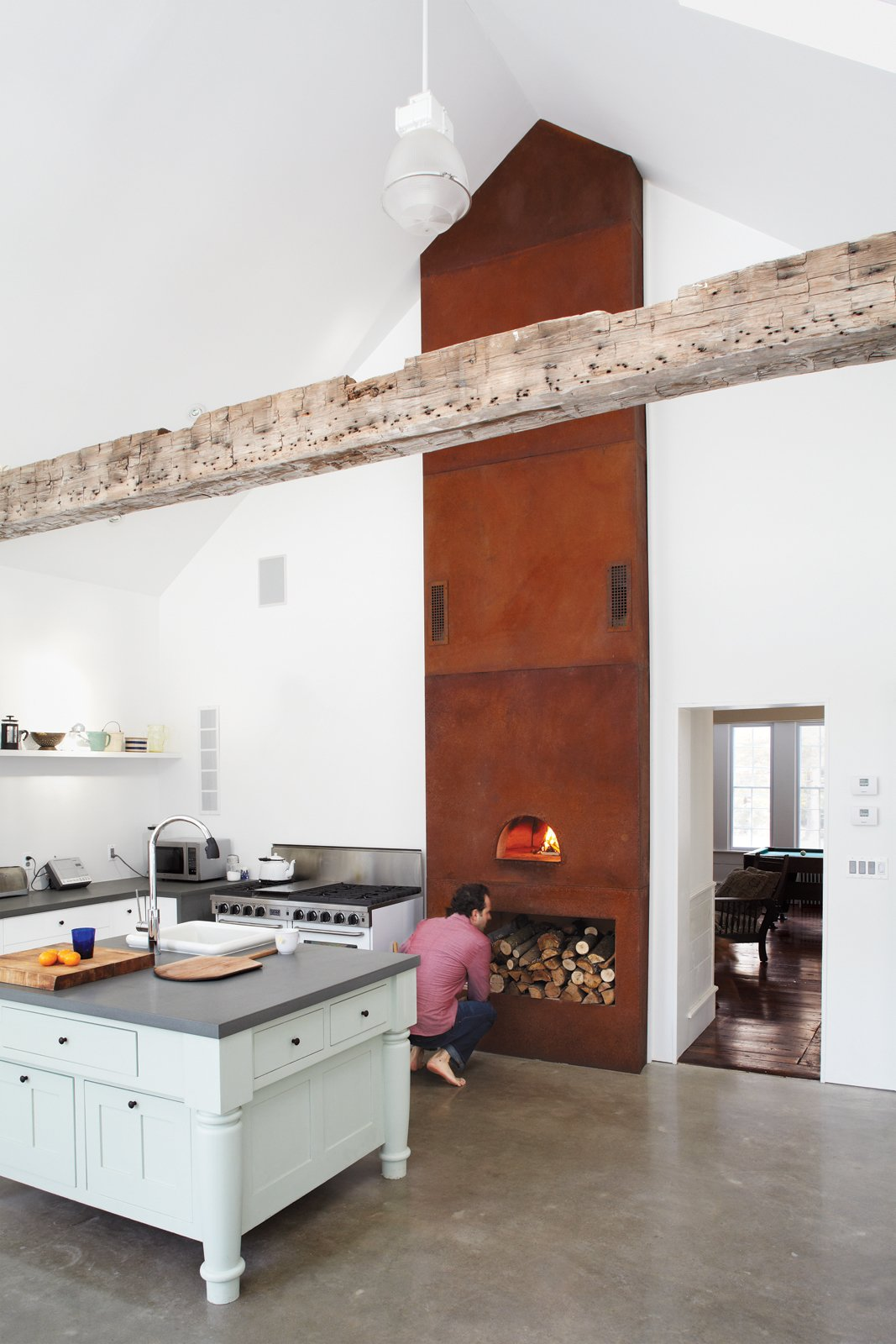 In the kitchen of Floating Farmhouse in Eldred, New York, a custom-built wood-fired oven extends up to the ceiling, accentuating its steep pitch. Photo by Mark Mahaney. Tagged: Kitchen, White Cabinet, and Concrete Floor.  Photo 2 of 12 in Hope Floats