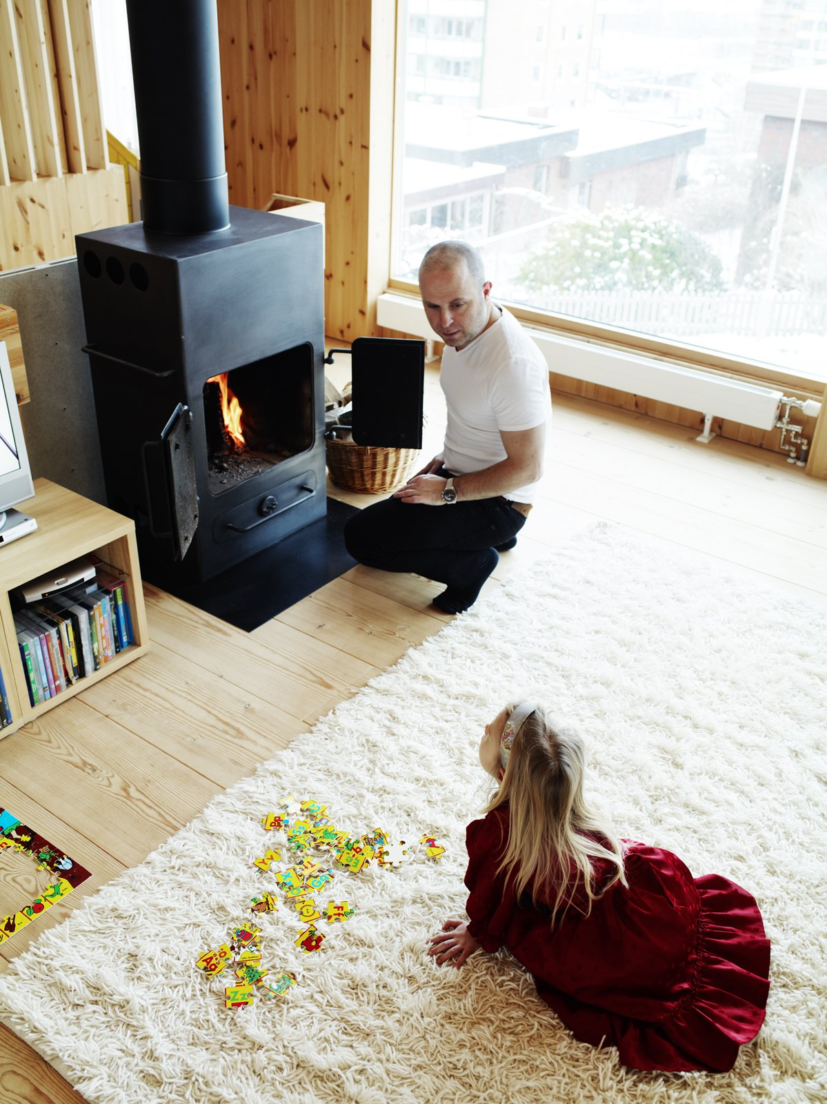Architect Per Bornstein and his daughter Velma relax in the living room. The woodburning stove was a second-hand store find. Photo by Pia Ulin. Tagged: Living Room, Wood Burning Fireplace, Standard Layout Fireplace, Light Hardwood Floor, Rug Floor, and Storage.  97+ Modern Fireplace Ideas by Dwell from Knotty by Nature