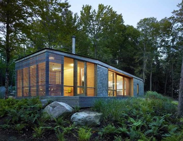 Sited on a lake near Bracebridge, Ontario, this small-footprint family cottage was designed by Toronto firm superkül to integrate with its natural surroundings and minimize its environmental impact. The clients, a married couple, had mixed feelings about going completely modern with their cabin's aesthetic, so the architects created a sculptural wood form to bridge the gap between traditional and contemporary. Photo by Shai Gil. Photo  of Stealth Cabin modern home