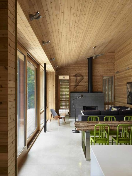 The cabin was designed so that the north half can be closed off when not in use to reduce energy consumption. When the northern half is closed, the radiant floor heating can be turned off and the main area can be heated by the high efficiency wood fireplace. Photo by Shai Gil. Photo 4 of Stealth Cabin modern home