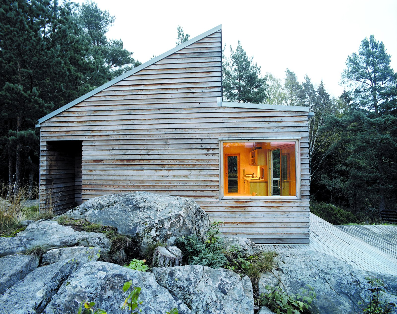 Woody35's distinct shape makes it stand out from its surroundings despite the modest size of the building. Tagged: Outdoor, Wood Siding Material, House, Boulders, Side Yard, Large Patio, Porch, Deck, and Wood Patio, Porch, Deck.  Sourcing Guide for Modern Prefab Companies in Europe by Kelsey Keith from A Prefab Cabin in Norway