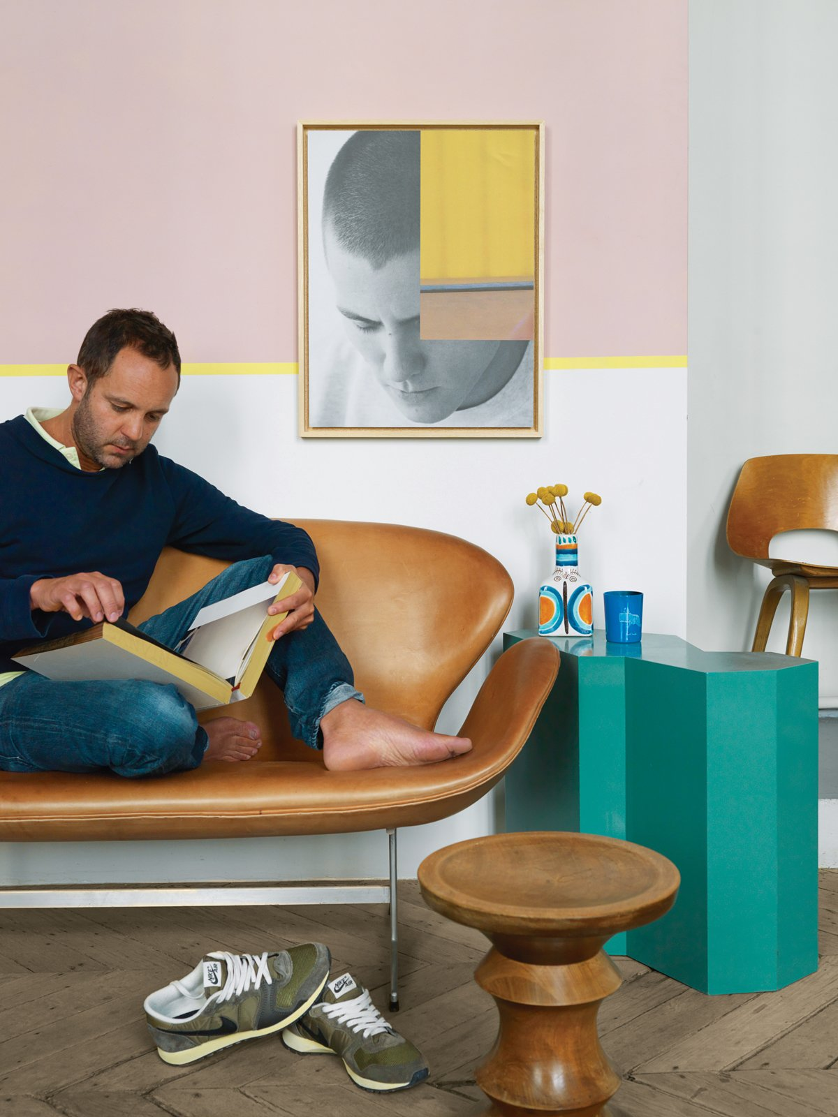 Aumas reads on a vintage Swan sofa by Arne Jacobsen. The teal side table is from a Berlin flea market; the walnut stool by Charles and Ray Eames is from an antique store in Brussels; Aumas himself made the art on the wall. A Furniture Collector's Renovated Flat in Paris - Photo 4 of 12