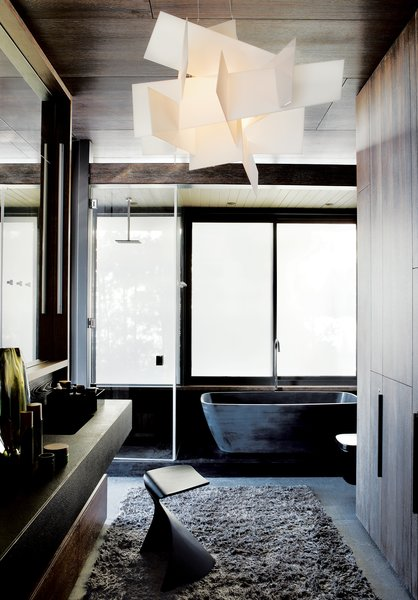 In the master bath, sandblasted windows let in light while retaining privacy. The tub is from Dado, the vanity and stool are from Ligne Roset, and the Big Bang light is from Foscarini.