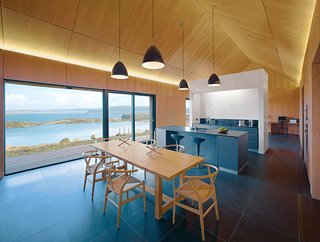 A Pitched-Roof Dwelling on Scotland's Isle of Skye - Photo 1 of 2 - Hans Wegner Wishbone chairs surround a custom table by Mary Arnold-Forster. The pendant lamps are by Bestlite.