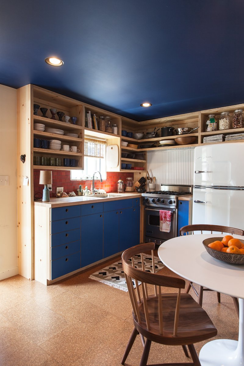 """The kitchen cabinetry echoes the new blue ceiling. The brick tile is from Heath Ceramics, as is the dinnerware. Behind the Viking stove is powder-coated corrugated metal (""""Very trailer,"""" says the designer). The refrigerator is from Big Chill. On the table is a bowl by Victoria Morris.  Photo 4 of 7 in A Modern Beachside Trailer Home in Malibu"""