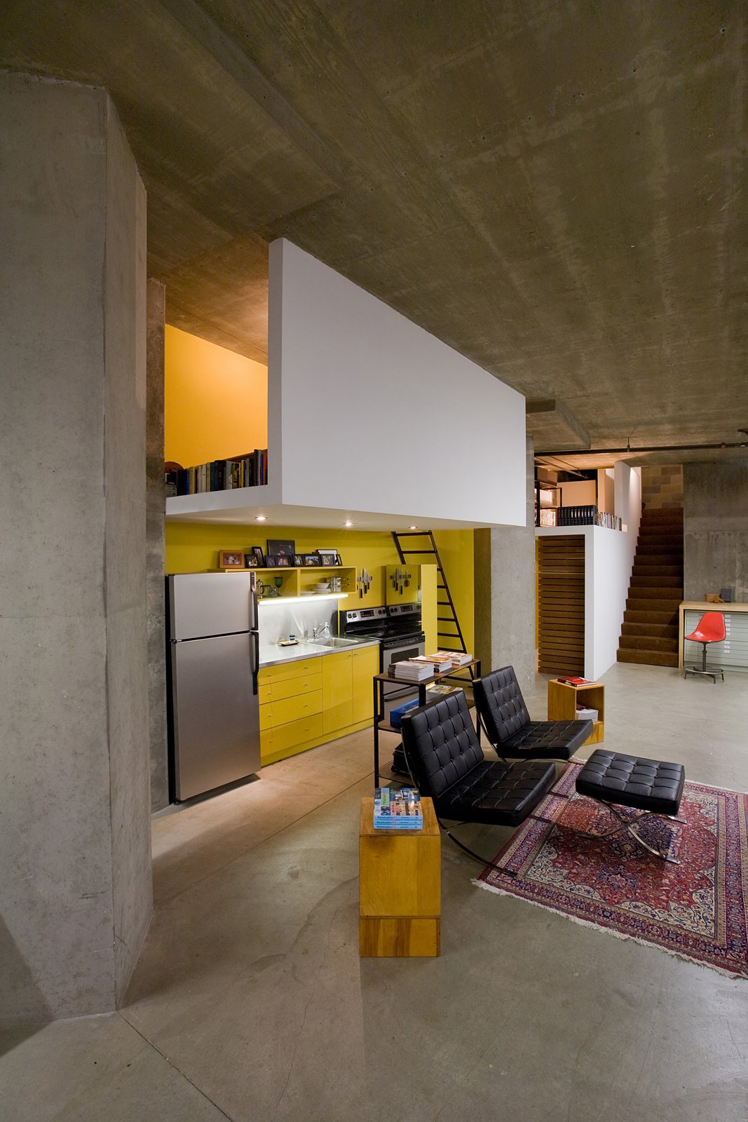 """The kitchen didn't really have a home,"" says Colkitt. His solution was to build the sleeping loft directly above it, giving the kitchen some architectural congruity, and implement recessed lighting into the dropped ceiling, also the underside of the floor of the sleeping loft. Like the reading loft, the sleeping loft is open on both sides to bring in light and air, with a single ladder leading up to it. ""The sleeping loft 'fold' is a complement to the reading loft 'fold'—they balance each other out,"" says Colkitt. Photo by Cheryl Ramsay Tagged: Kitchen, Colorful Cabinet, and Concrete Floor. Clever Loft Spaces for Small Places by Diana Budds"