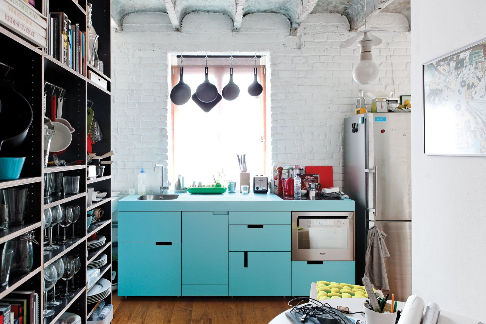 "The budget was nearly as tight as the space in this cheerful renovation of a 516-square-foot flat in Bratislava. The centerpiece of Lukáš Kordík's new kitchen is the cabinetry surrounding the sink, a feat he managed by altering the facing and pulls of an off-the-rack Ikea system. The laminate offers a good punch of blue, and in modernist fashion, Kordík forwent door handles in favor of cutouts. ""I wanted the kitchen to be one simple block of color without any additional design,"" he says.  Photo 1 of 8 in A Little Apartment Gets a Solid Renovation"