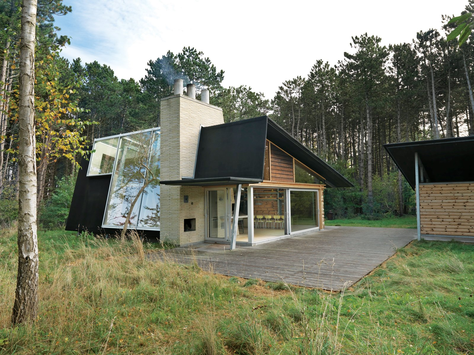After living on and studying a woodsy acre of land in North Zealand, Denmark, architect Jesper Brask cleared a stand of pine trees and, from the timber, built a getaway open to its surroundings. The house, which Brask shares with his wife, Lene, and sons, Kristian, Jens, and Niels, is used mainly in summer, when the weather is optimal for throwing open the glass doors.