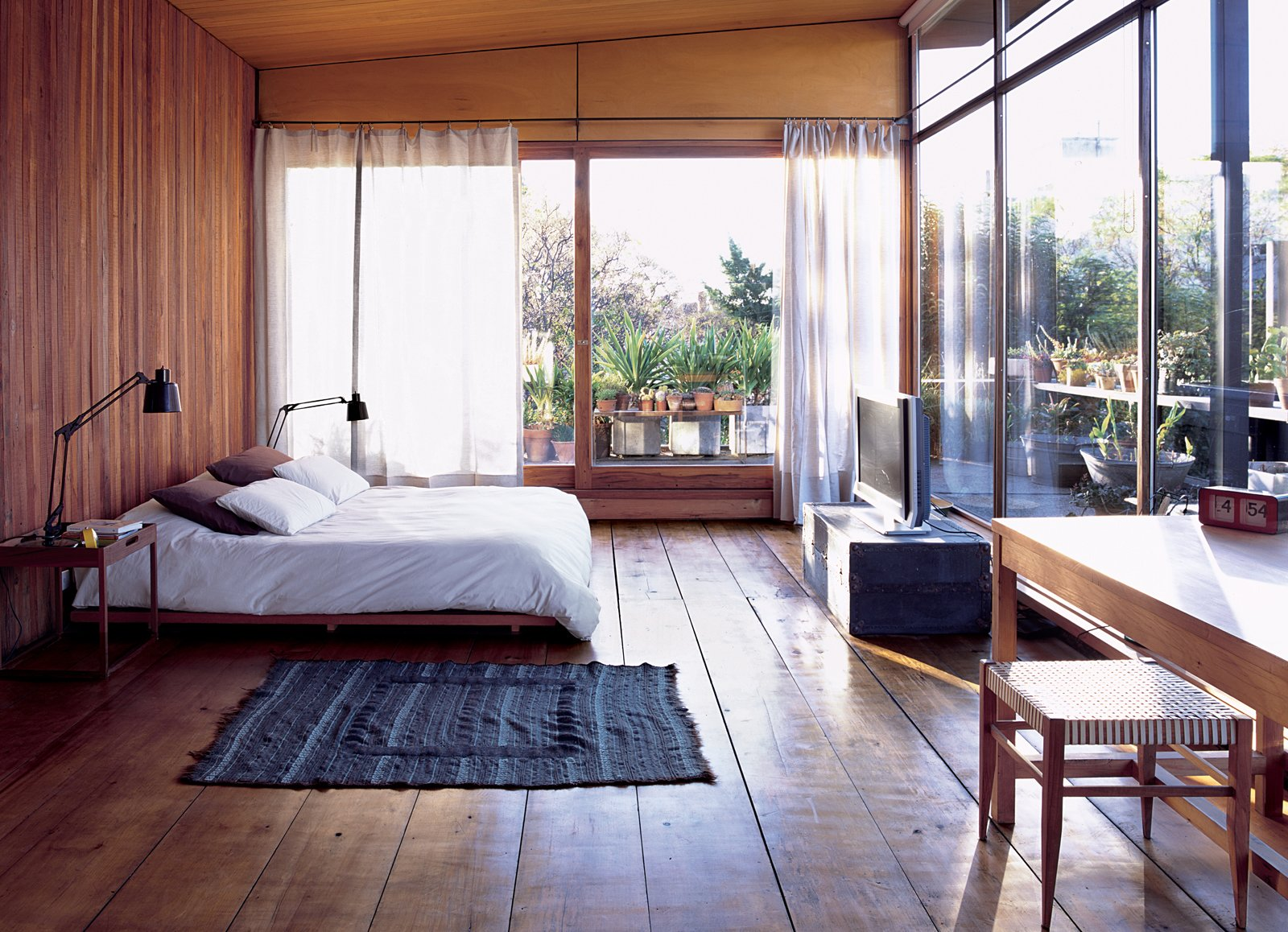 A COZY AND MODERN INDOOR-OUTDOOR BEDROOM IN BUENOS AIRES  In Argentinean architect and furniture designer Alejandro Sticotti's bedroom, dappled sunlight and reclaimed-wood floors and walls give the room a warm, peaceful feel. Tagged: Bedroom, Bed, Medium Hardwood Floor, and Table Lighting.  Bedroom by Elmaqroll  from Net Assets