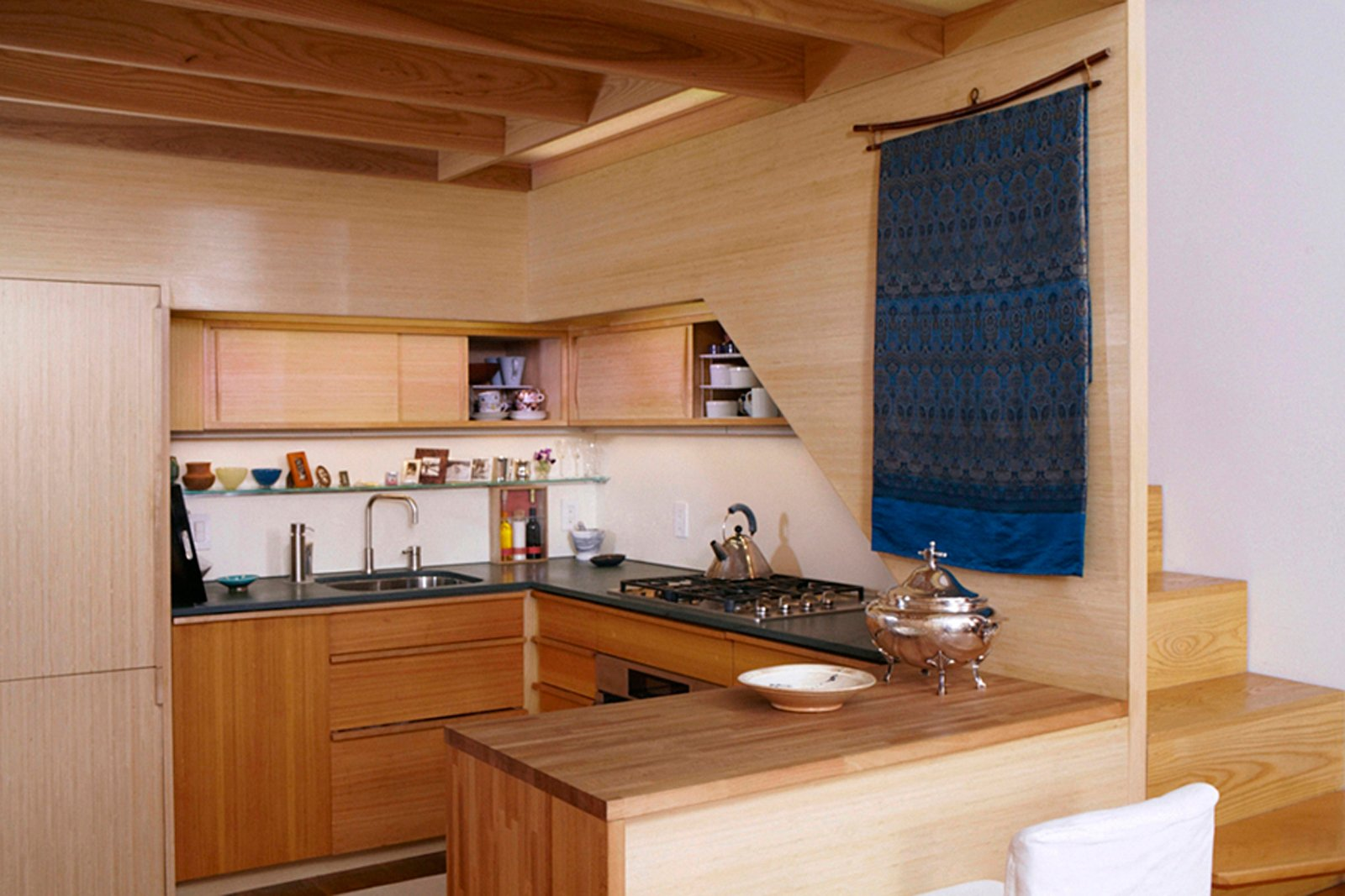 In this truly tiny apartment, a 240-square-foot shoebox of an apartment in NYC with a sleeping loft over the kitchen, architect Tim Seggerman went straight to his toolbox to craft a Nakashima-inspired interior. Photo by David Engelhardt. Tagged: Kitchen, Wood Counter, Wood Cabinet, Refrigerator, Drop In Sink, Range, and Wall Oven.  Photo 6 of 8 in Space-Saving Wood-Paneled Apartment in Manhattan